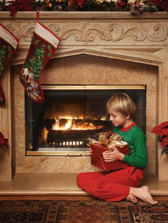8 year old boy sitting beside the fireplace with a wrapped Christmas gift in his lap Stock Photo