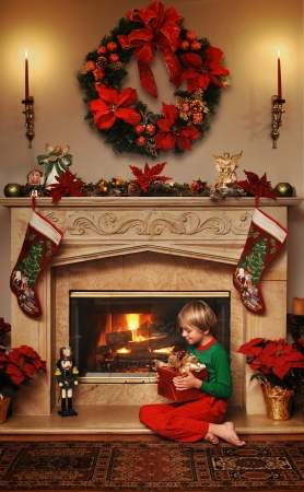 and guessing: 8 year old boy sitting beside the fire with a wrapped Christmas gift in his lap