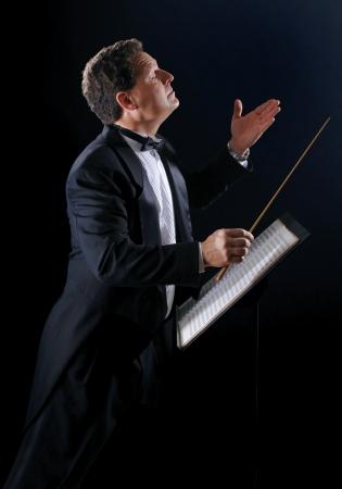音楽指揮者、タキシードを着て、黒の背景にオーケストラの写真