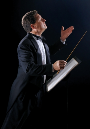 orchestrate: A photo of a music conductor wearing a tuxedo, conducting an orchestra on a black background