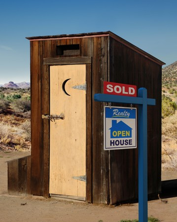 A realestate sign showing a dumppy out-house sold in the desert. photo