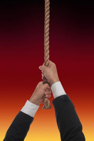 frazzled: man hanging at end of his rope over fire Stock Photo