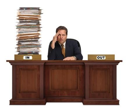 ein in-Box auf einem Corporate deskwith überfüllt mit einem Berg von Papierkram mit mit einem überarbeiteten Mann dahinter trägt einen Anzug und Krawatte auf weißem Hintergrund