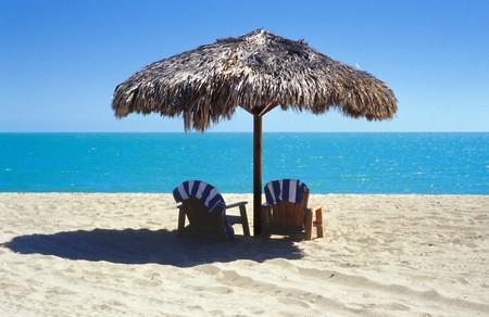cabane plage: Tiki parapluie avec deux chaises Adirondack sur la plage.