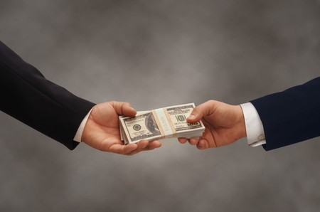 debt collection: Two hands of businessmen passing a stack of dollars