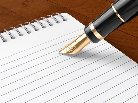 A note pad and old fashoned fountain pen on a wooden table