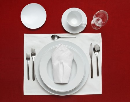 placemat: Full table place setting on a red table cloth