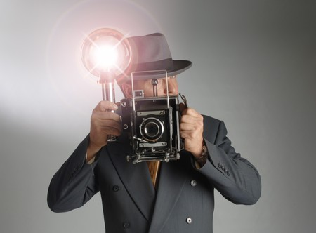 fedora hat: Retro 1940s stylephotographer wearing a Fedora hat and holding a vintage camera with flash bulb flashing