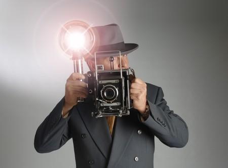 Retro 1940 stylephotographer het dragen van een Fedora hoed en met een vintage camera met flits lamp knippert Stockfoto