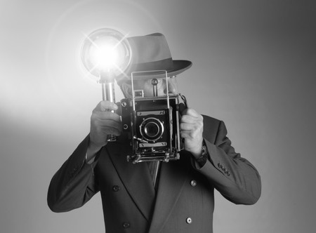 Black & White shot of a retro 1940s stylephotographer wearing a Fedora hat and holding a vintage camera with flash bulb flashing