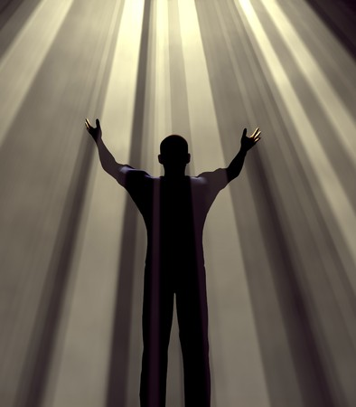 Man holding arms up in praise against light rays photo