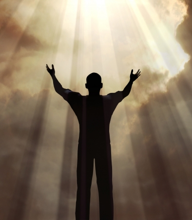 Man holding arms up in praise against a sunburst