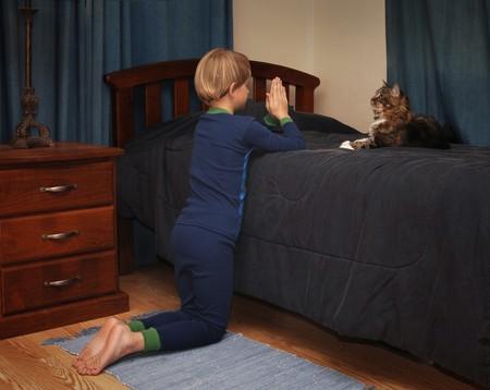 bedside: boy kneeling at bedside saying prayers in pajamas Stock Photo