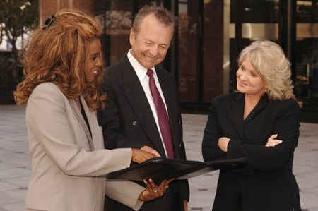 confer: Two professional women and one businessman confer outside an office building