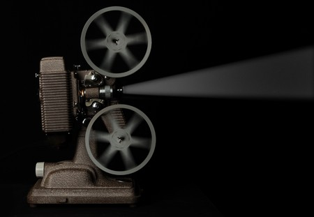 vintage movie projector running against dark background photo