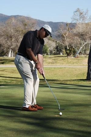 ゴルファーのゴルフ場のパッティング グリーンに穴に、ゴルフボールを置く 写真素材