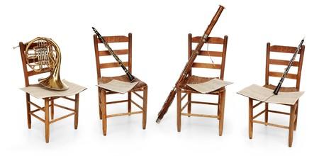 clarinete: Corno francés, clarinete, fagot y oboe sentados en sillas vacías con partituras sobre fondo blanco