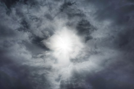 emanating: Sunburst in clouds with faint Christ figure emanating from center