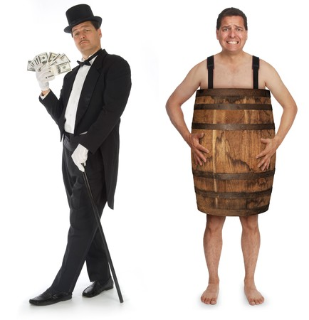 Man in tuxedo, top hat and cane fanning himself with stacks of money standing next to the same man who is using a barrel as clothing Stock Photo
