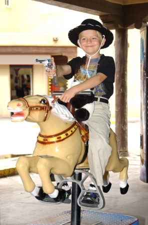 6 year old boy wearing cowboy attire riding a vending machine pony                                Stock Photo