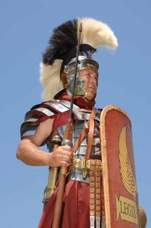 cascos romanos: Primero soldado romano del siglo I en la armadura, el rango de Optio dispar� contra un cielo azul Foto de archivo