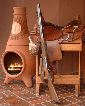 kiva: Saddle, rifle and kiva fireplace still life depicting New Mexico