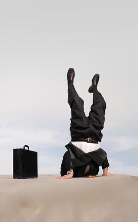 struś: Biznesmen stojących na głowie z jego głową w piasku