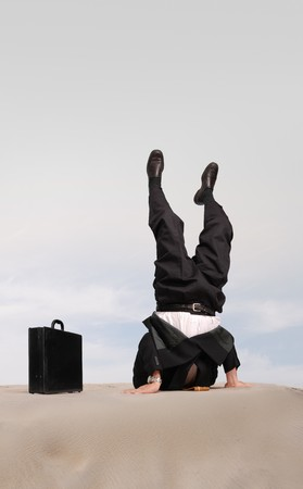 wimp: Businessman standing on his head with his head in the sand Stock Photo