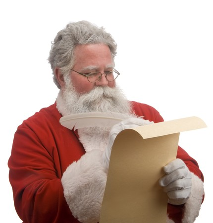 Santa on a whit background checking the toy list Stock Photo - 9519783