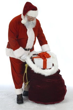 Full Santa removing a present from his gift sack Stock Photo - 9519824