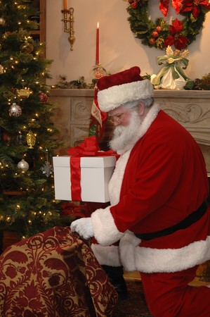 Santa placing a gift under the tree from his sack of toys photo