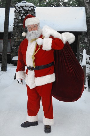 Full length Santa standing in snow with sack of toys  Stock Photo - 9519854