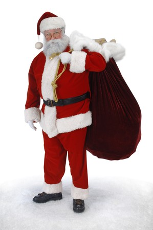 Full length Santa standing in snow with sack of toys on a white background photo