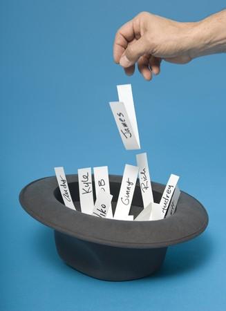 Hand, werfen ein Stück Papier mit einem Namen auf Sie in einen Hut mit anderen Namen Standard-Bild - 7054093