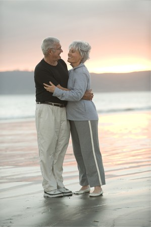 Senior couple hugging on the beach at dusk