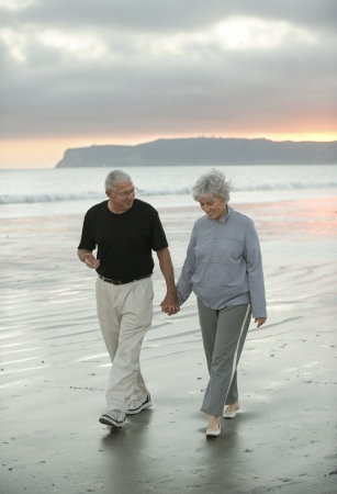 Senior couple enjoying a walk on a beach in California Stock Photo