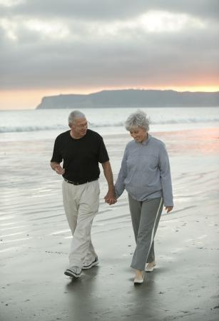 boomers: Senior couple enjoying a walk on a beach in California Stock Photo