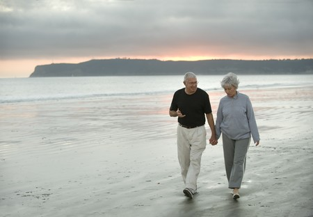 Senior husband and wife walking along the beach in California