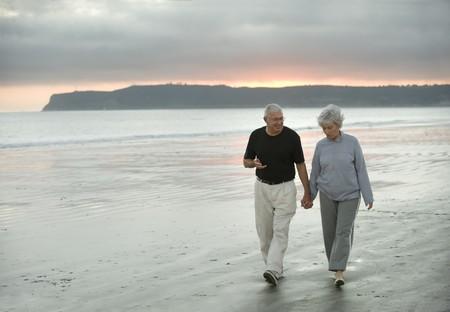 boomers: Senior husband and wife walking along the beach in California