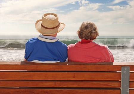 A senoir adult couple sitting at a benchand, enjoying their time at the beach.