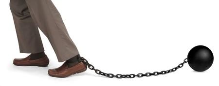 shackled: piernas del hombre que arrastra una bola y la cadena  Foto de archivo