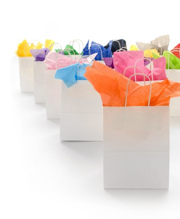 White shopping bags with colorful tissue paper on a white background