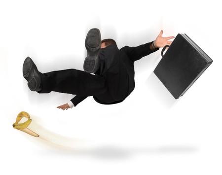 Geschäftsmann, Rutschen und fallen aus einer Bananenschale auf weißem Hintergrund