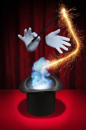 White gehandschoende handen houden een tover staf boven een goochelaar cilinderhoed produceren vonken en rook op een rode achtergrond  Stockfoto