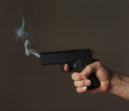 assassinate: hand holding smoking pistol on dark background