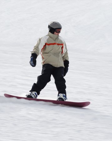 A Man Snowboarding fast down a hill. Stock Photo