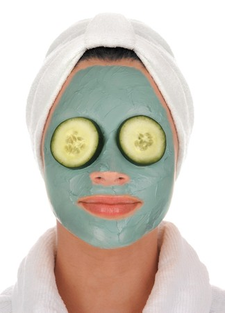 rejuvenated: front view of a beautiful young woman in white terry cloth bathrobe and turban with deep sea mud mask facial treatment and cucumbers over eyes on white background                     Stock Photo