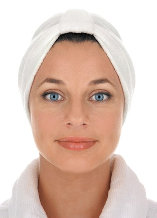 rejuvenated: front view of a beautiful young woman in white terry cloth bathrobe and turban looking clean, fresh and pampered on white background                     Stock Photo