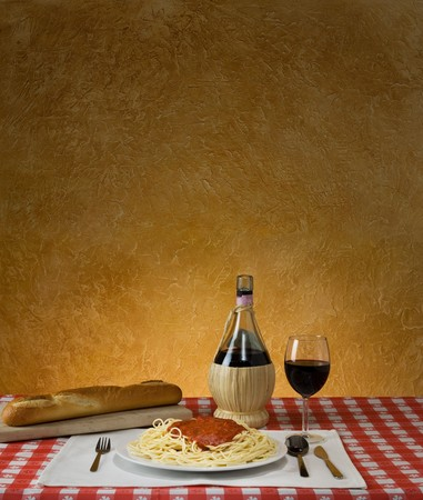 Spaghetti dinner with a baguette and Chianti on a red checkered table cloth with ample background for copy space photo