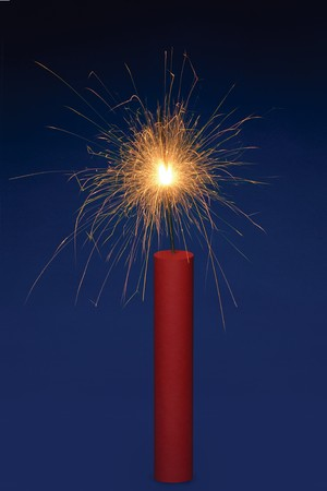 Stick of dynamite with a lit fuse on a blue background photo
